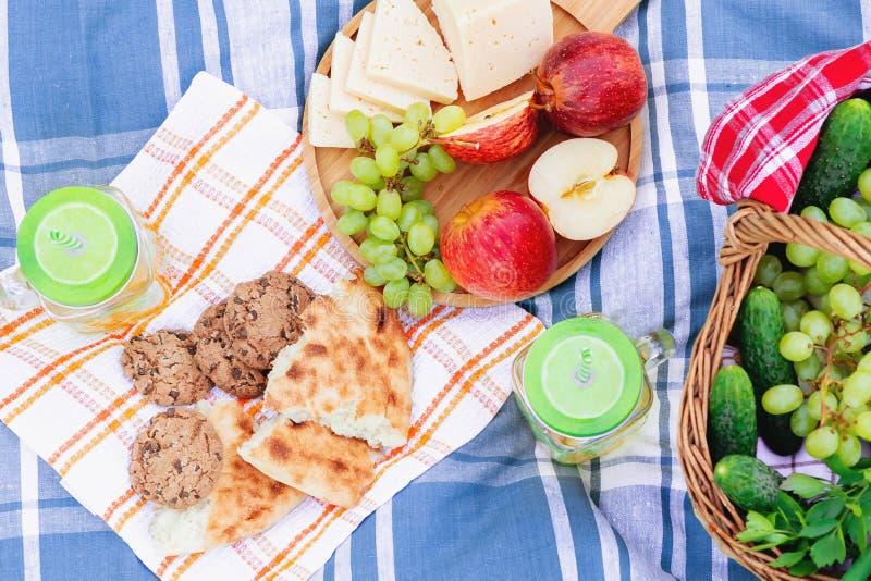 在草在一个夏日-篮子,葡萄,乳酪,面包,苹果的野餐-夏天室外休闲的概念 库存图片