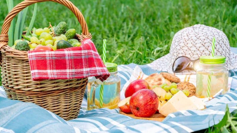 在草在一个夏日-篮子,葡萄,乳酪,面包,苹果的野餐-夏天室外休闲的概念 库存照片