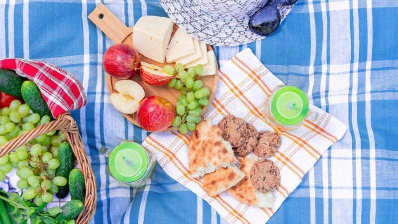 在草在一个夏日-篮子,葡萄,乳酪,面包,苹果的野餐-夏天室外休闲的概念 免版税库存图片