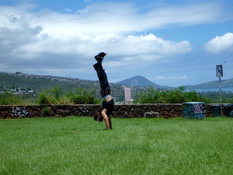 在草地的人手倒立在Kaimuki顶部 库存图片