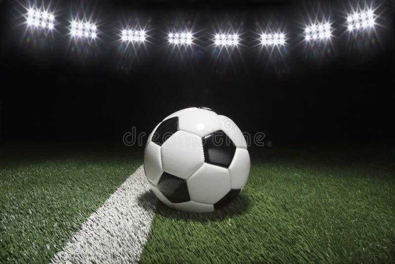 在草地的传统足球在光下在晚上 免版税库存图片