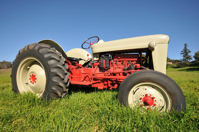 在草地的老农用拖拉机 免版税库存图片