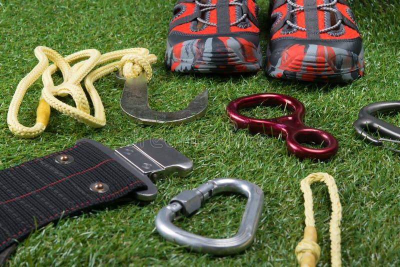 在草坪、旅游项目、鞋子、绳索上升的和carabiners的背景 库存图片