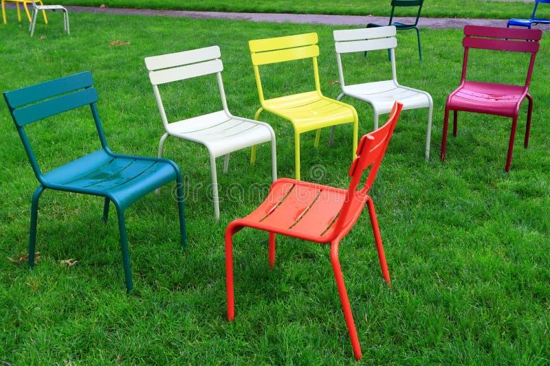 在草坪的五颜六色的椅子 免版税库存照片