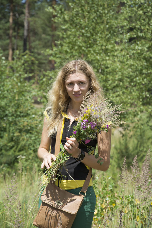 在草坪的夏天女孩拿着野花花束  库存图片