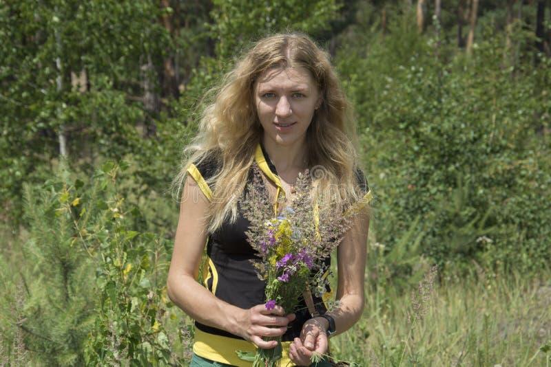 在草坪的夏天女孩拿着野花花束  免版税图库摄影
