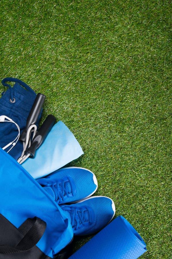 在草坪的绿色背景的谎言蓝色体育请求与衣物和运动器材跑和跳跃的高 免版税库存图片