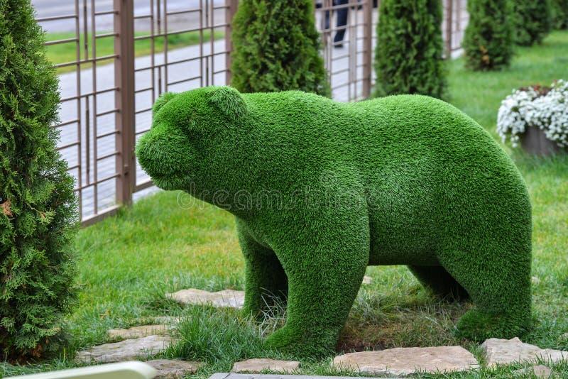 在草坪的绿草熊装饰雕塑在庭院里 免版税库存图片