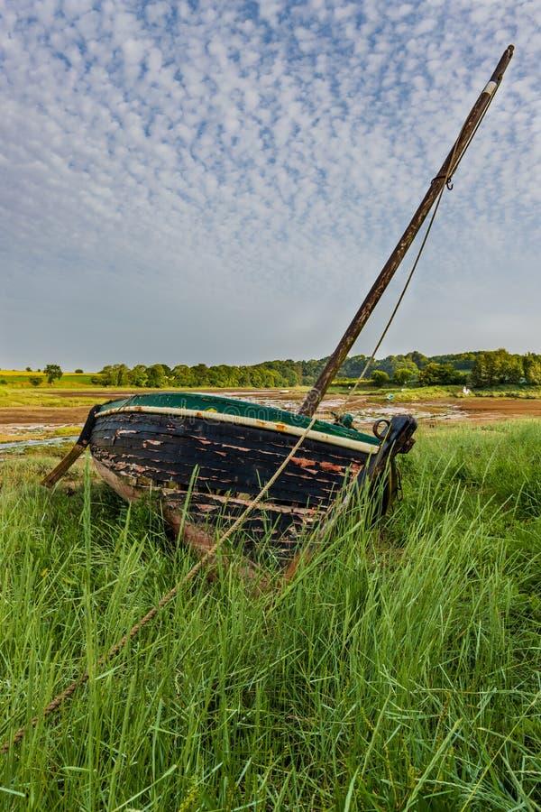 在草搁浅的小船 免版税库存照片