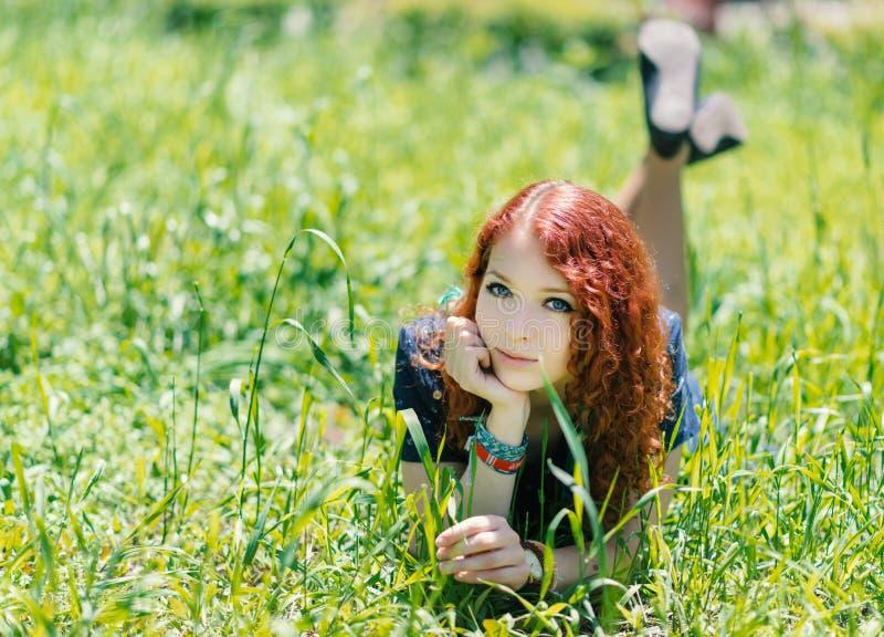 在草放置的红头发人女孩 库存图片