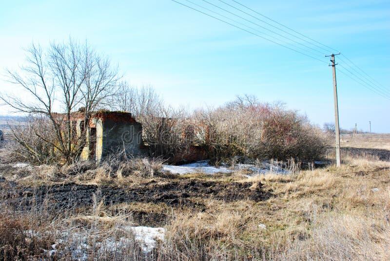 在草甸上的蓝色没有叶子、干草和熔化的雪的多云天空有被放弃的被破坏的砖房子的和树 免版税图库摄影