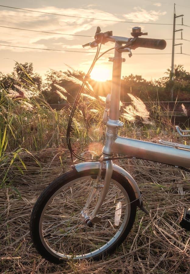 在草甸停放的自行车可折叠 库存照片