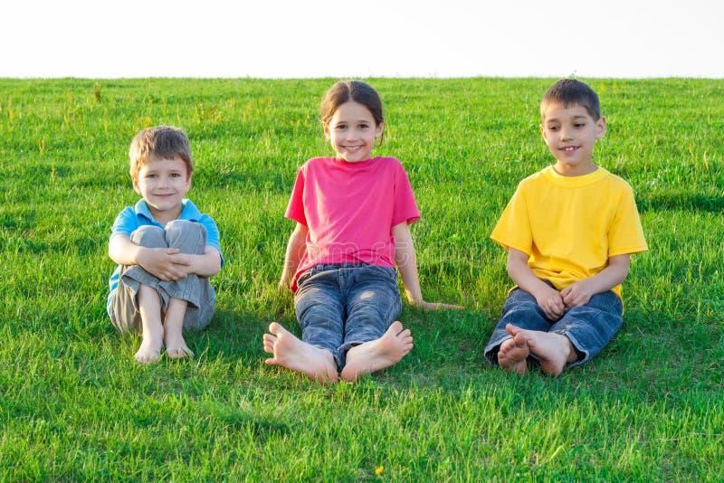 在草甸的三个微笑的孩子 图库摄影