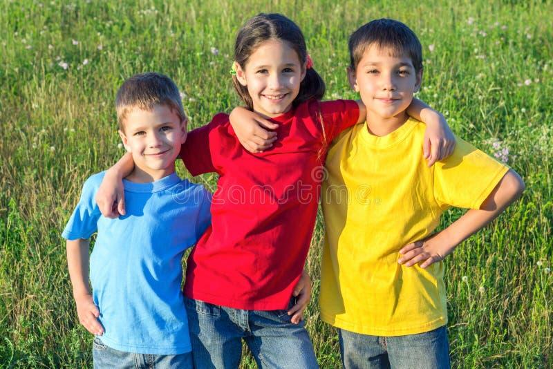 在草甸的三个微笑的孩子 免版税库存照片