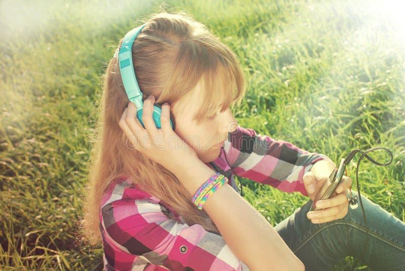在草甸的女孩听的音乐葡萄酒样式的 库存图片