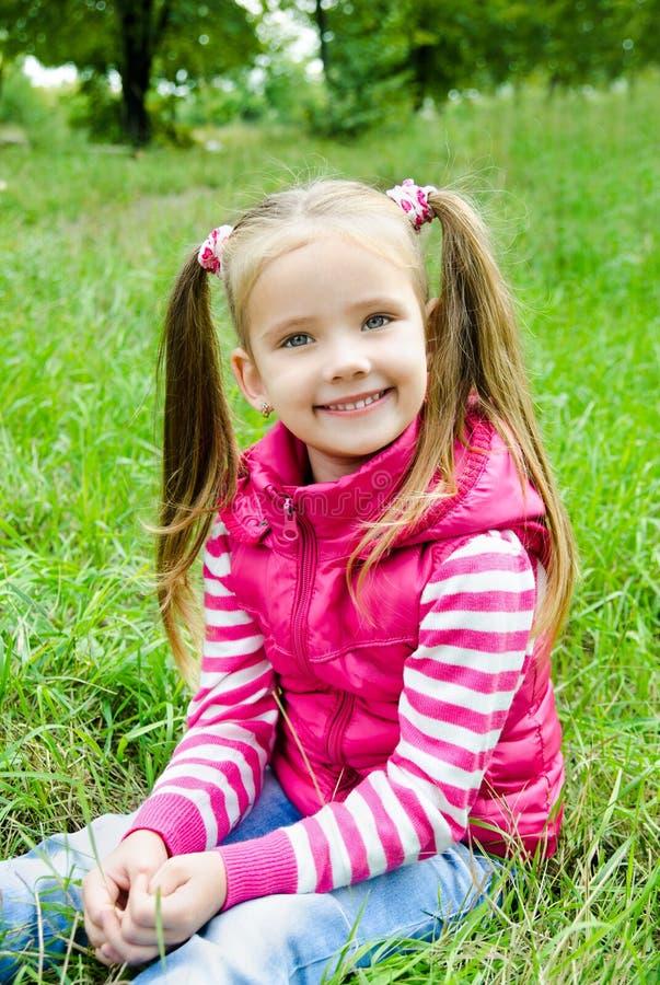 在草甸的草的逗人喜爱的微笑的小女孩 免版税库存照片