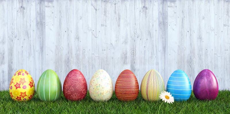 在草的五颜六色的复活节彩蛋有白色木背景 库存图片