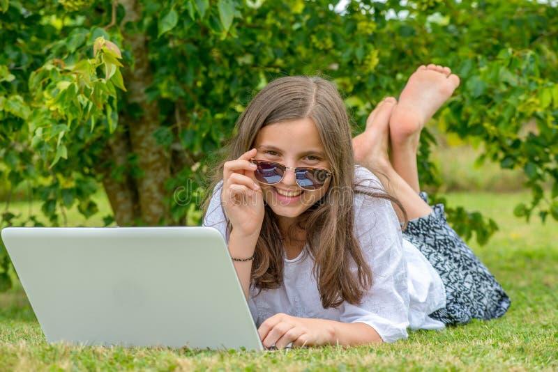 在草的十几岁的女孩使用膝上型计算机 免版税库存照片