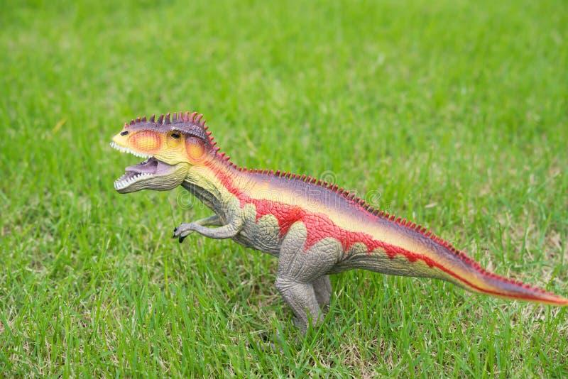 在草的南方巨兽龙玩具 库存照片