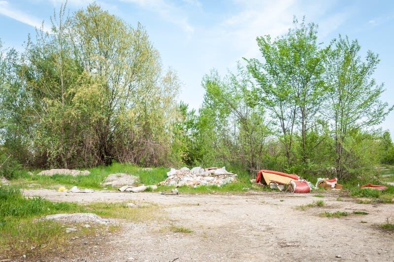 在草的垃圾堆在森林生态灾难概念污染自然附近和城市停放与废弃物和破烂物 免版税图库摄影
