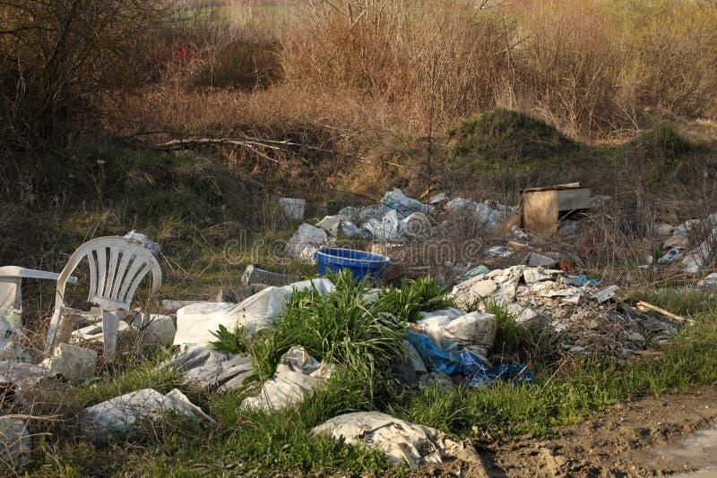在草的垃圾堆在非法路附近 库存照片