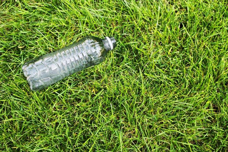 在草的塑料瓶 免版税库存图片