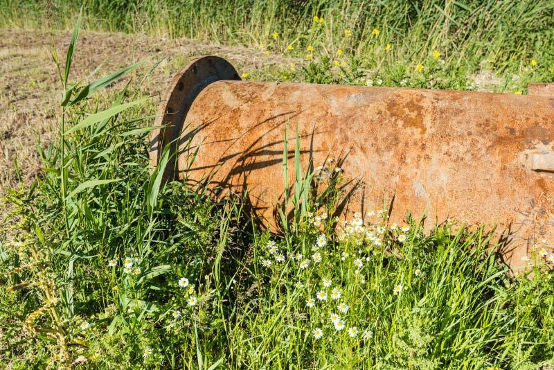 在草的大和生锈的管子 库存照片