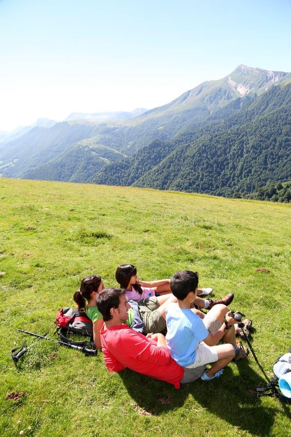 在草的家庭放松在山 库存照片