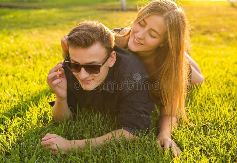在草的少年有吸引力的夫妇微笑和获得乐趣 库存图片