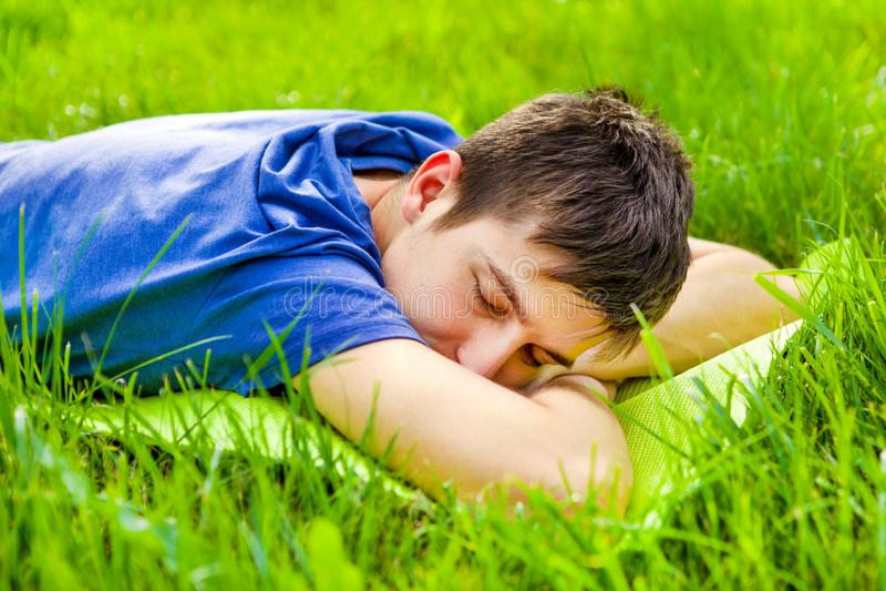 在草的年轻人睡眠 库存照片