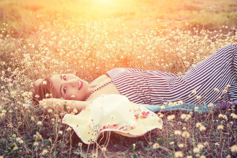 在草的年轻性感的妇女临近她的帽子和面带笑容对加州 免版税库存图片