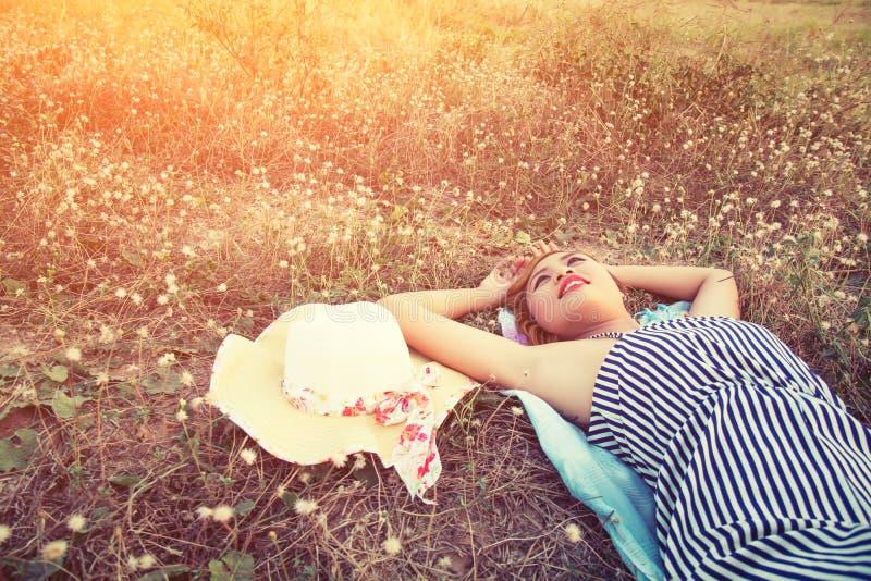 在草的年轻性感的妇女临近她的帽子神色入s 库存照片