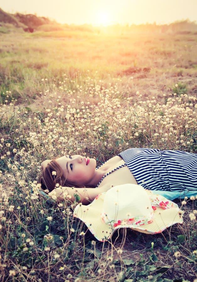 在草的年轻性感的妇女临近她的帽子神色进入sk 库存照片