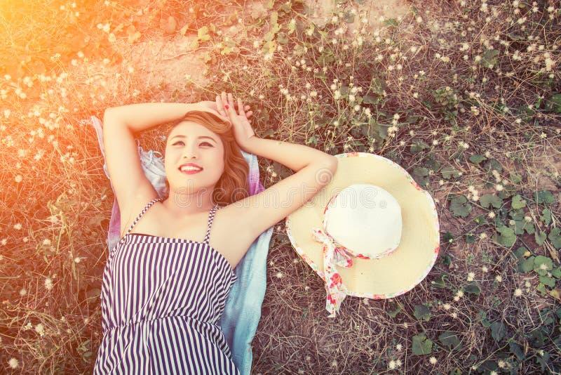 在草的年轻性感的妇女顶视图临近她的帽子神色 免版税库存照片