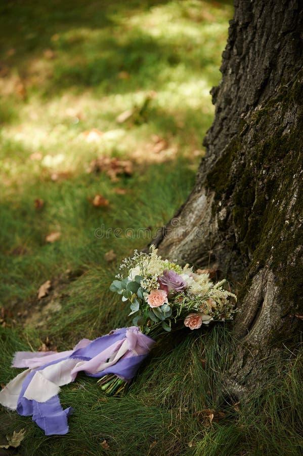 在草的新娘花束在树附近 免版税图库摄影