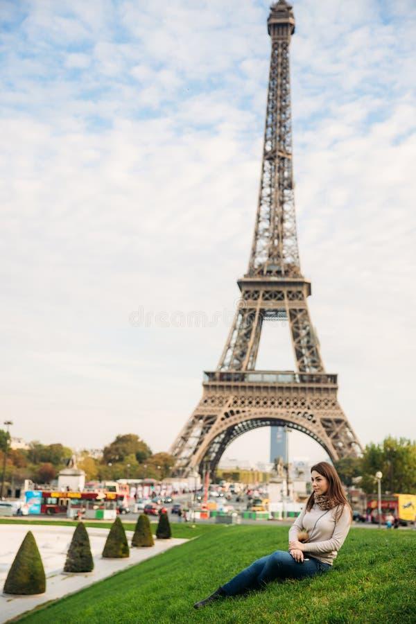 在草的有吸引力的小姐sist 埃佛尔铁塔背景  免版税库存图片