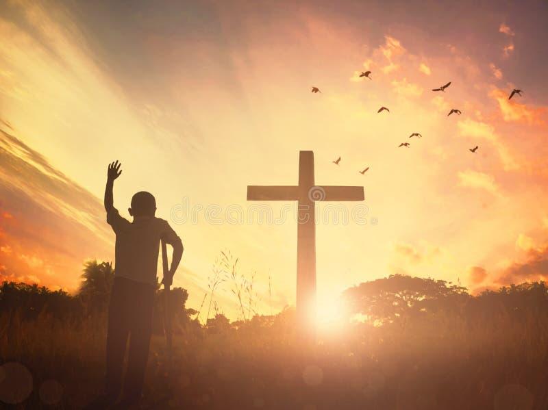 在草的概念概念性黑发怒宗教标志剪影在日落或日出天空 免版税库存照片