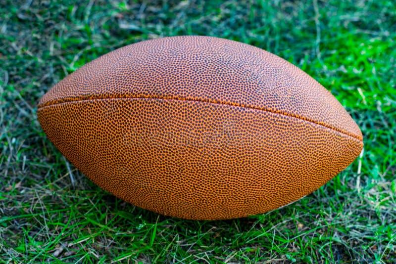 在草的橄榄球球 橄榄球的运动器材 免版税库存照片