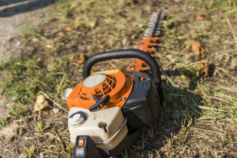 在草的橙色汽油发动机便携式的锯 图库摄影