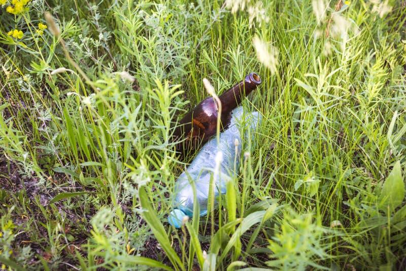 在草的玻璃和塑料瓶 免版税图库摄影