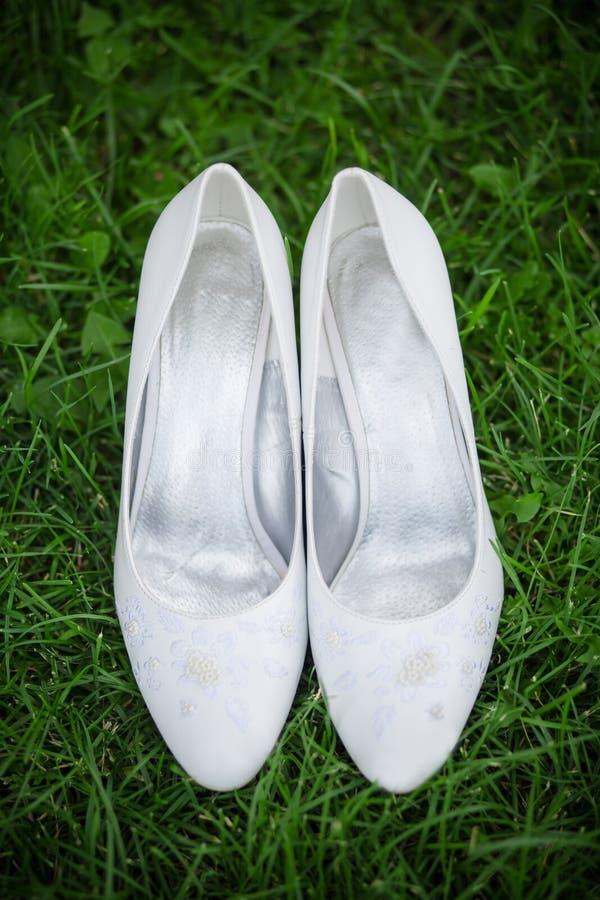 在草的白色鞋子 免版税库存照片