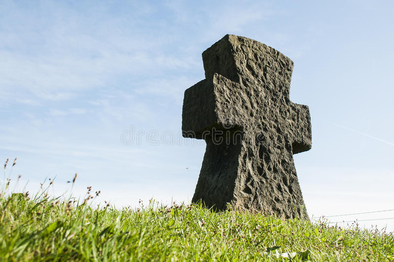 在草的石十字架与蓝天 免版税库存照片