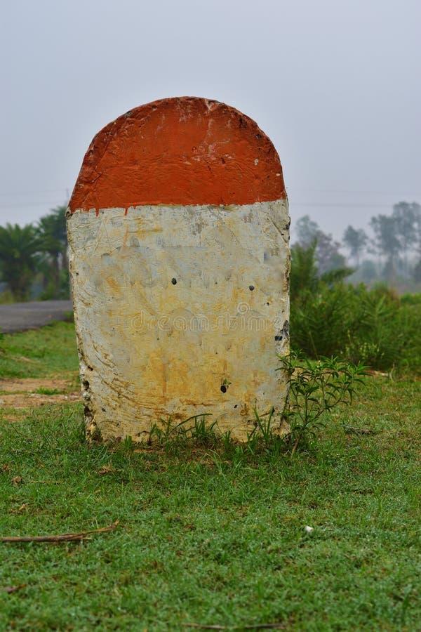 在草的空白的英里石头在路附近,有印刷品第一百标志的 库存照片