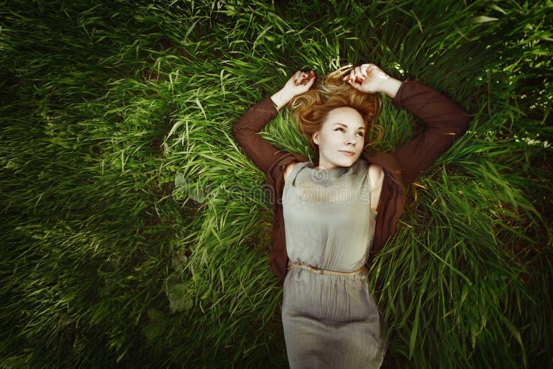 在草的美丽的少妇。减速火箭的颜色。夏天, 免版税库存图片