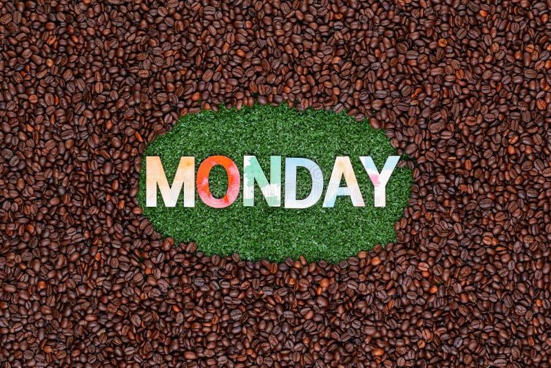 在草的词星期一与咖啡豆 免版税库存照片