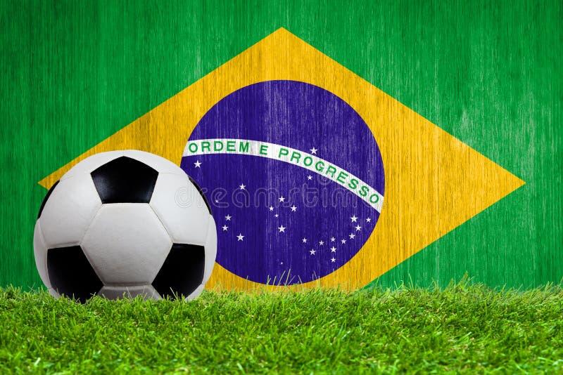 在草的足球有巴西旗子背景 免版税图库摄影