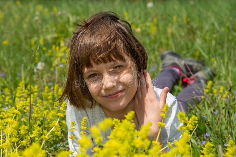 在草的逗人喜爱的女孩和花和笑 库存照片