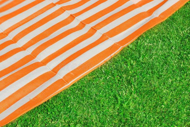 在草的野餐或海滩席子 免版税图库摄影