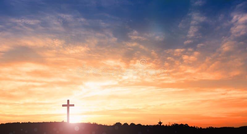 在草的黑发怒宗教标志剪影在日落或日出天空 免版税库存照片