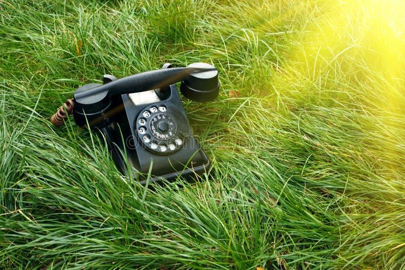 在草的黑老减速火箭的电话与阳光 免版税图库摄影
